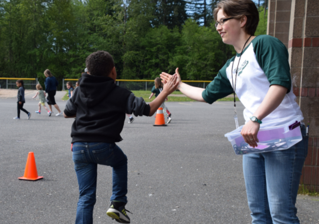 Teacher reaches out to high five a student at Track Stars